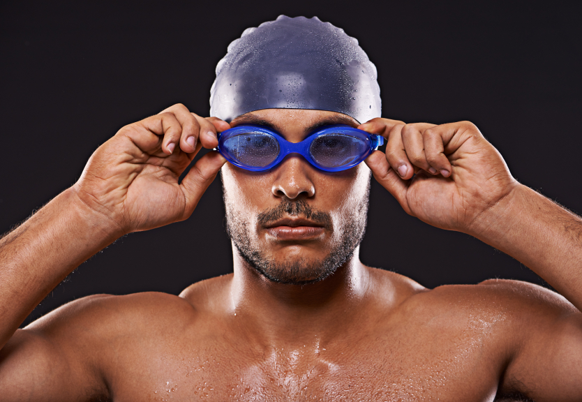 Studio shot of a handsome swimmer holding his goggles